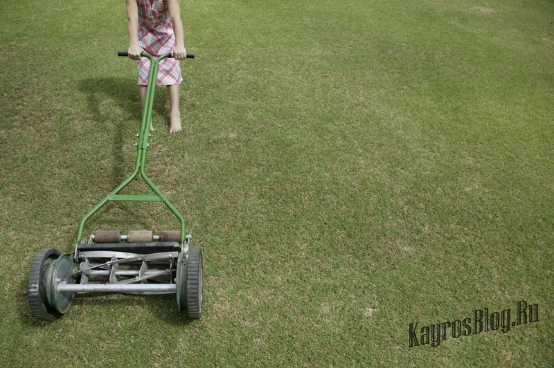 Girl Holding onto Lawn Mower --- Image by © Royalty-Free/Corbis